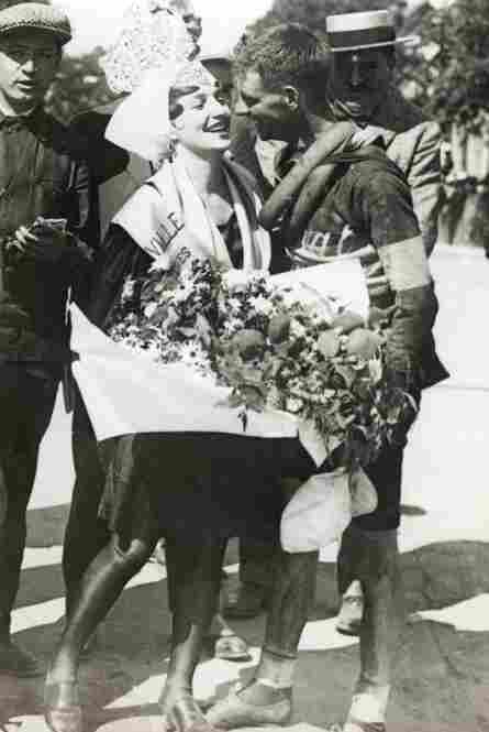 The rewards for finishing a stage include kisses and flowers from the local beauty for Hubert Opperman, after the 6th stage of the 1928 Tour de France. The infamous yellow jersey was introduced in 1919.