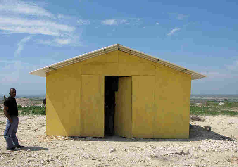 "A guard stands outside a prototype ""transitional"" housing model at the resettlement camp in Corail-Cesselesse. World Vision along with several other aid agencies has developed these small dwellings, intended to house families of up to five people."