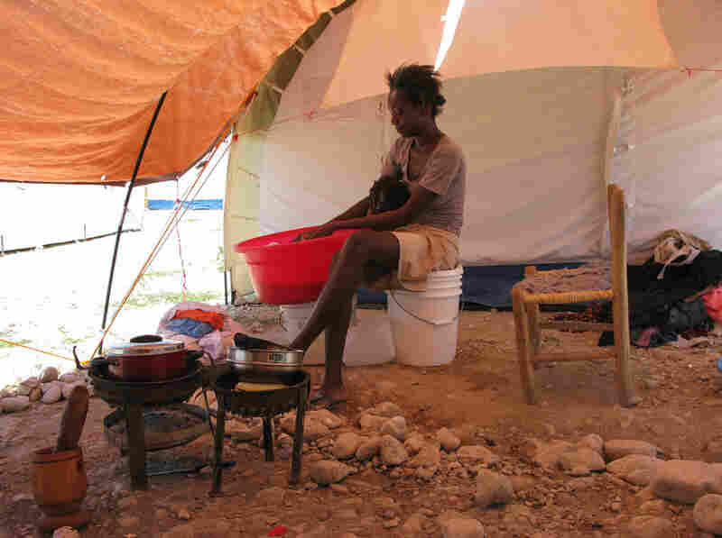 A Haitian woman cooks beans and washes clothes outside her tent. A tarp protects her and her daughter from the scorching sunlight.