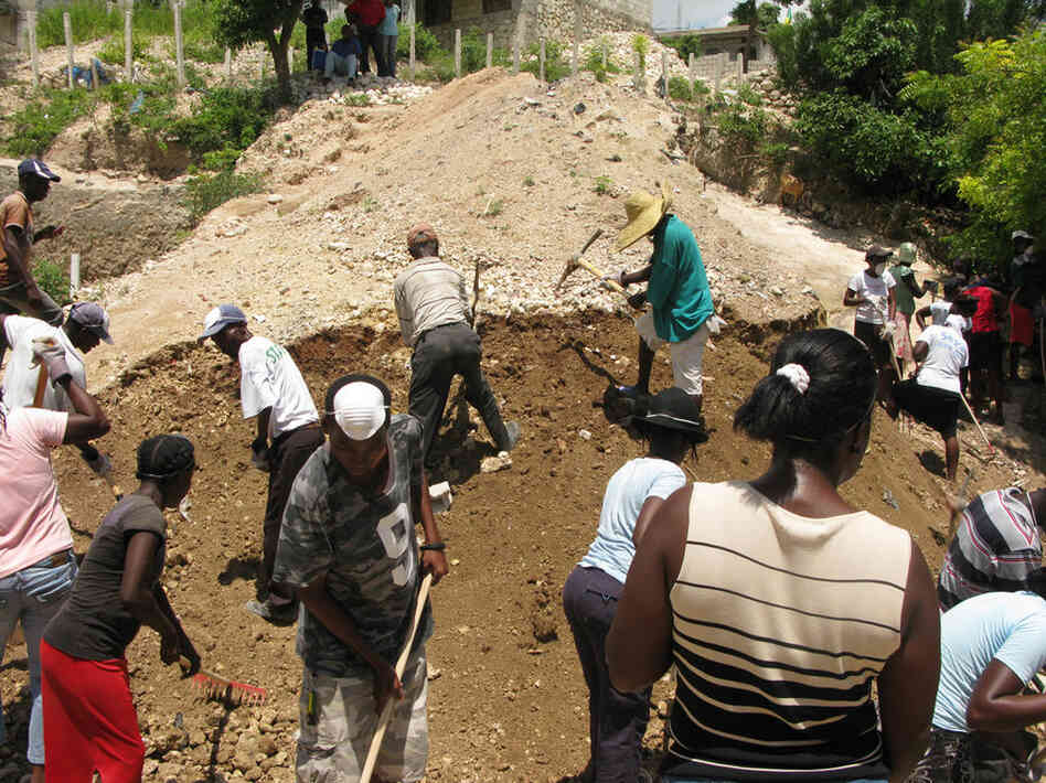 MFD camp in Haiti's capital is a hive of activity as residents work on drainage channels in preparation for the hurricane season. Teams break up the soil with picks, sweep trash and dig drainage channels in the cash-for-work program.