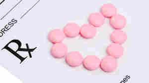 Pills form a heart on a prescription pad.