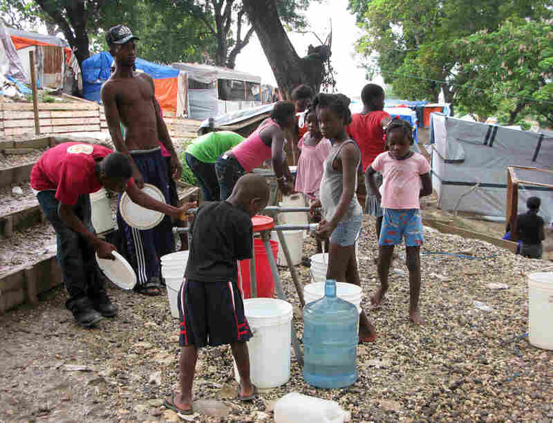 Late in the afternoon at Petionville Club camp, children gather to fill water jugs. The water is purified and safe to drink.