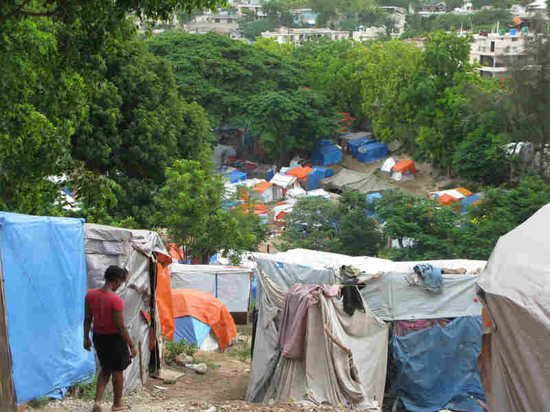 A woman walks down a path in the crowded Petionville Club camp in Port-au-Prince.