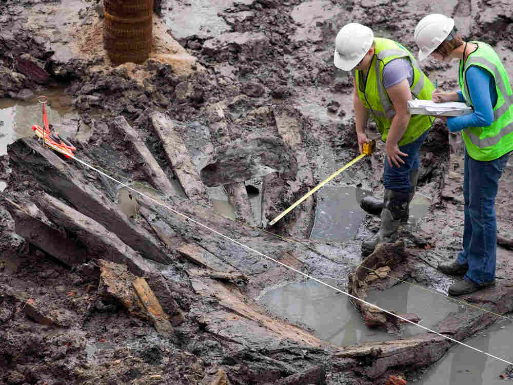 Archeologists take measurements of the wood hull of what is thought to be an 18th century ship.