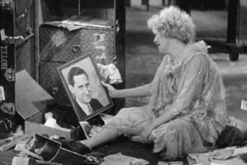 "Helen Morgan (as Kitty Darling) sings ""What Wouldn't I Do for That Man?"" to a photo of Fuller Mellish (as Hitch Nelson) in Applause"