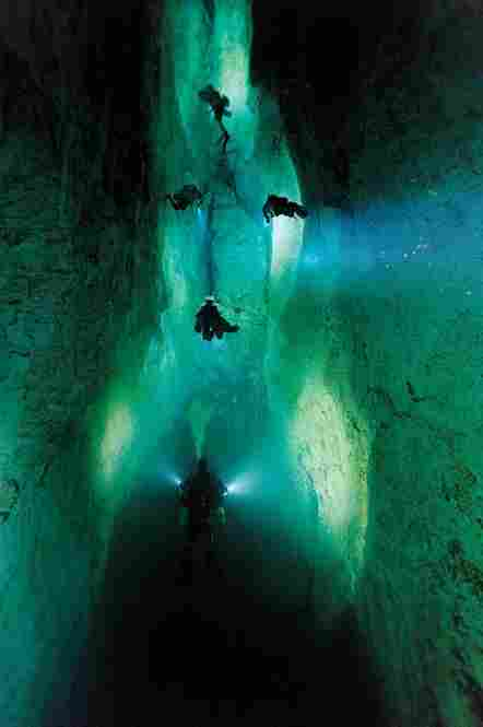 Divers illuminate a passage in Stargate, a blue hole on Andros Island.