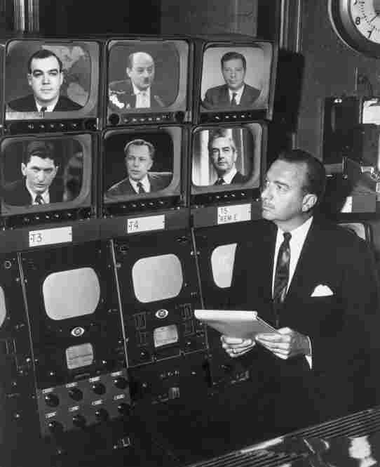 Broadcast journalist Walter Cronkite stands before a group of television monitors showing the CBS News Correspondents for the show Eyewitness. Schorr is seen at the top right. Also pictured: Charles Kuralt, David Schoenbrun, Marvin Kalb, Winston Brudett and Howard K. Smith.