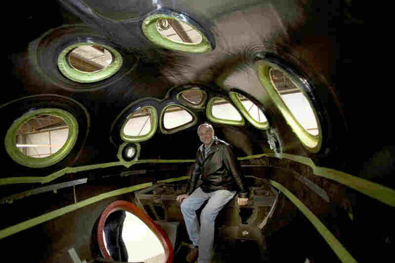Burt Rutan, the aerospace engineer behind SpaceShipOne and SpaceShipTwo, sits inside SpaceShipTwo's cabin. Its interior is more passenger friendly than SpaceShipOne's, with a cabin big enough for six passengers.