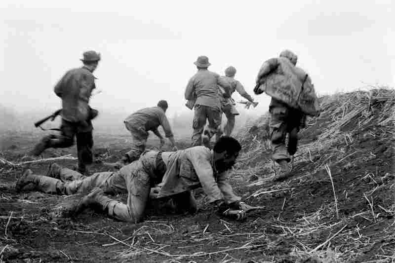 Soldiers scramble and duck artillery fire during the siege of Khe Sanh, Vietnam.