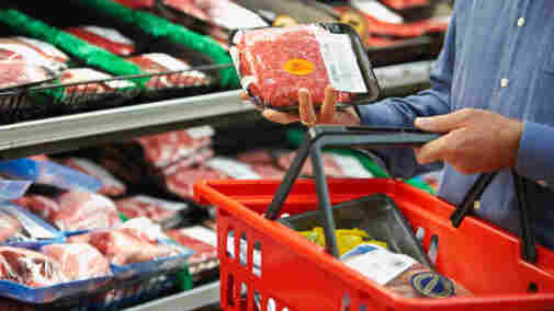 man inspects package of meat