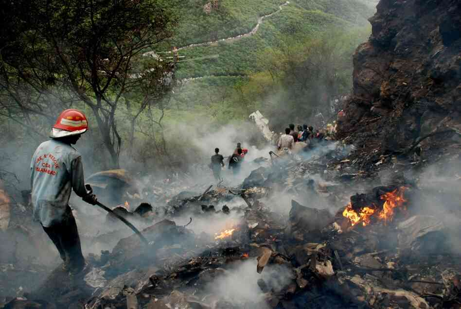 Pakistani rescue workers search the wreckage. Attempts to reach the site were initially hampered by muddy conditions.