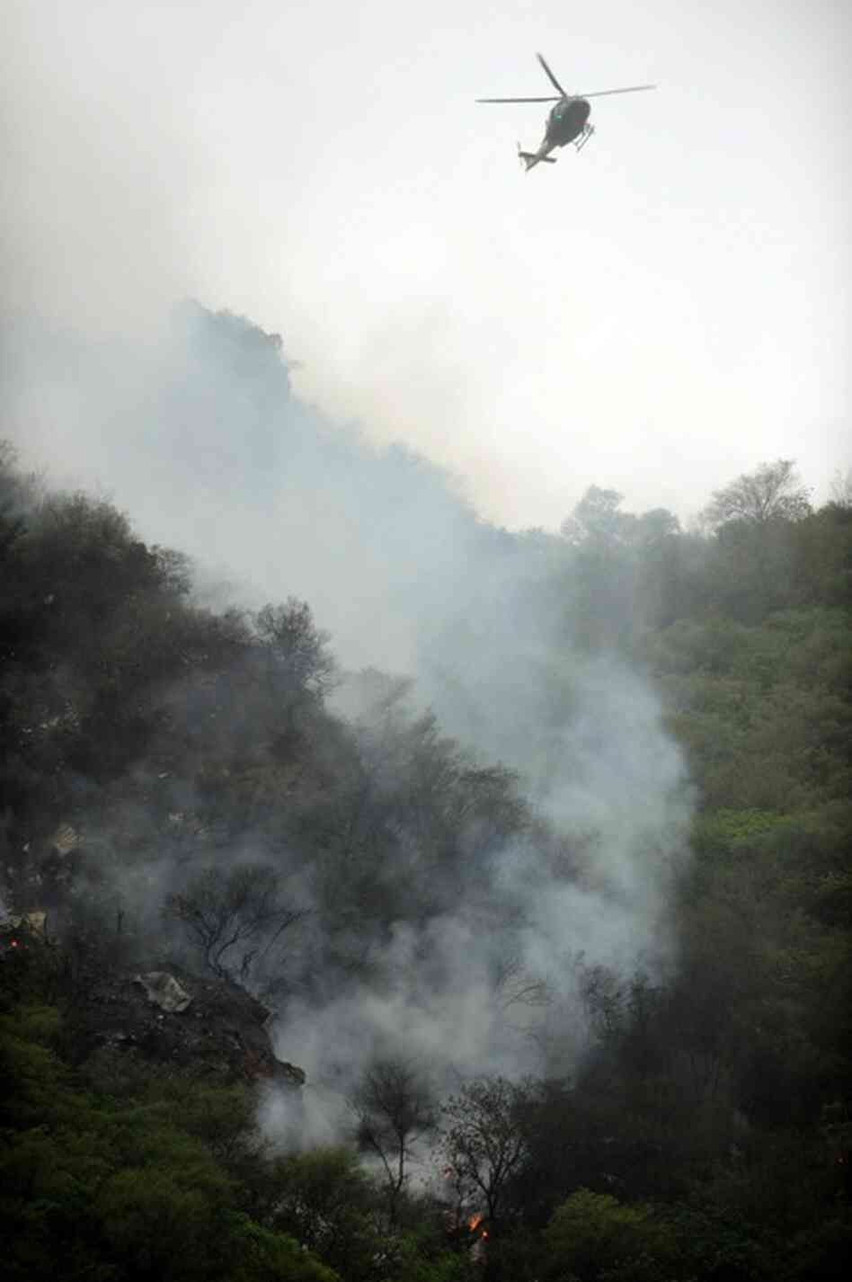 A Pakistani rescue helicopter flies above the crash site.