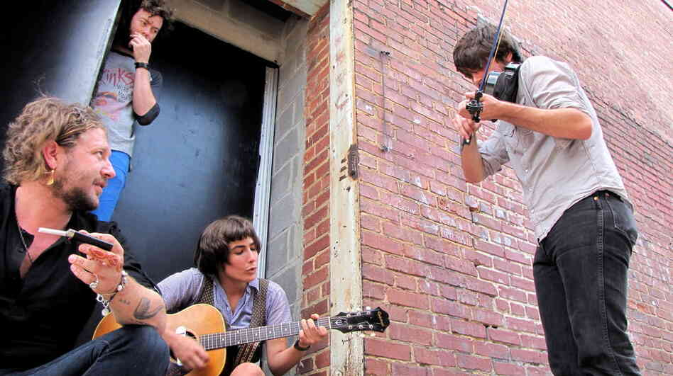 NPR Intern Alex Spoto jams with the band in the alley and later gets invited on stage to play.