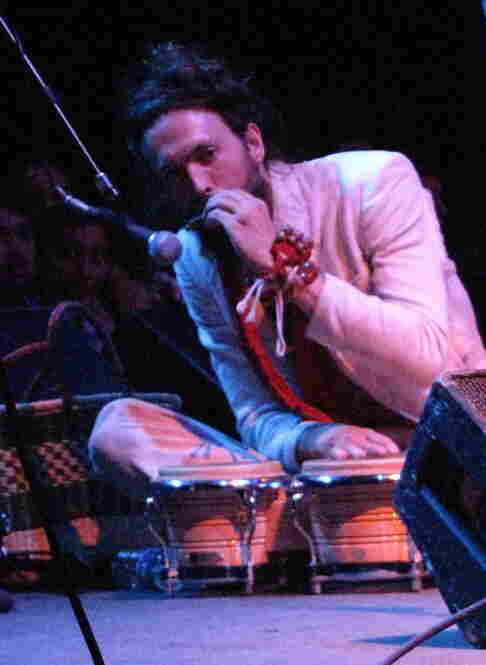 Lead singer Alex Ebert sits with his harmonica on stage.