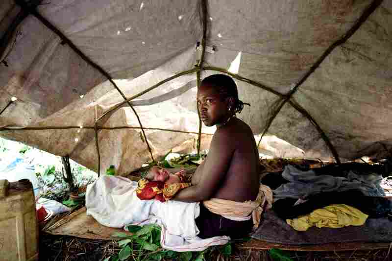 A woman who gave birth while fleeing the LRA holds her newborn baby in a makeshift tent near a road in Yambio, Western Equatoria state.