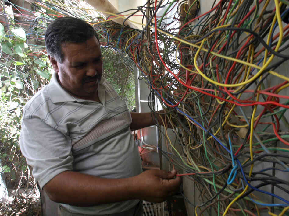 An Iraqi electrician checks the wires le