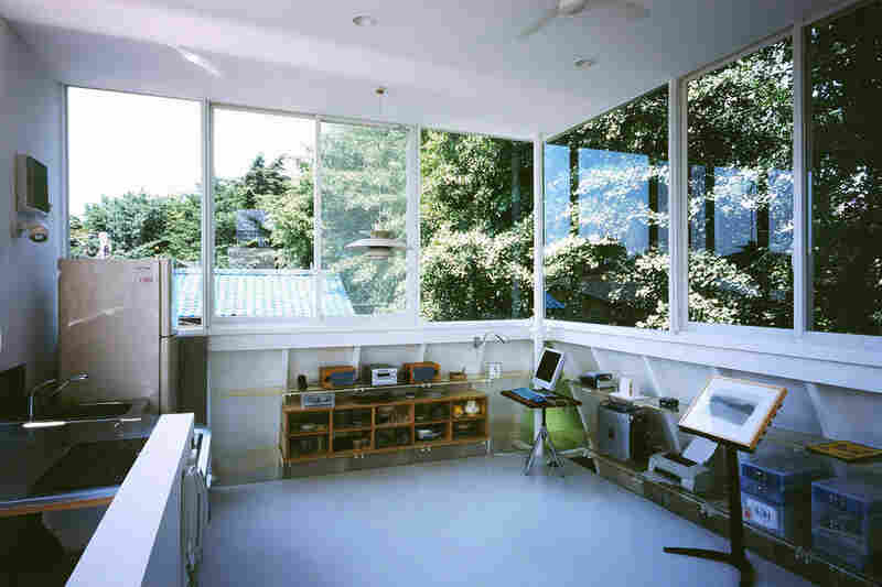 """The sun-filled third floor of """"Penguin House,"""" with windows on all sides, contains the combined living room and kitchen."""