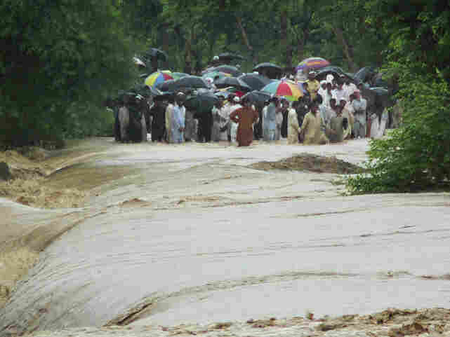 People wait to cross a flooded road in Bannu, Pakistan.