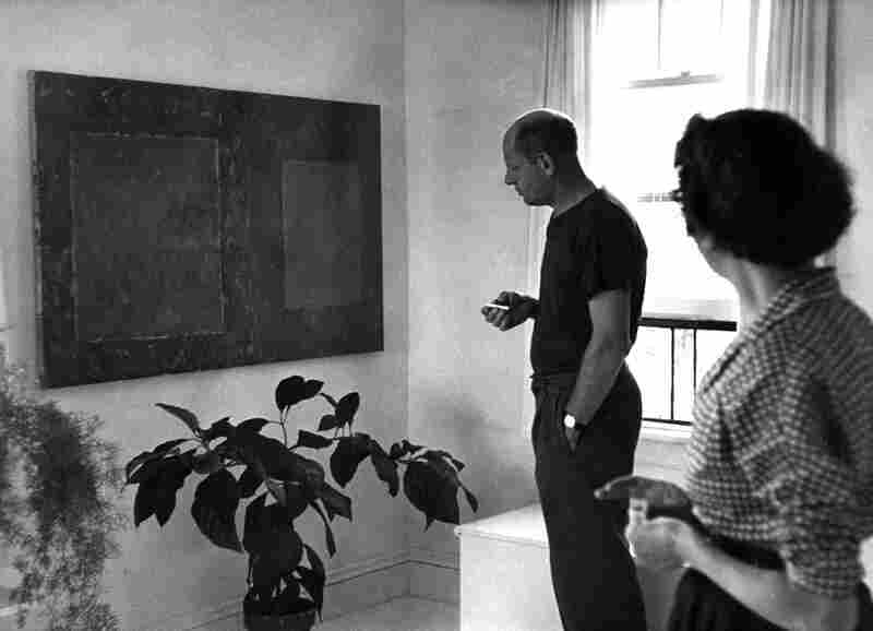 Pollock and Lee Krasner in their bedroom, looking at an untitled 1950 painting by Krasner, August 1953