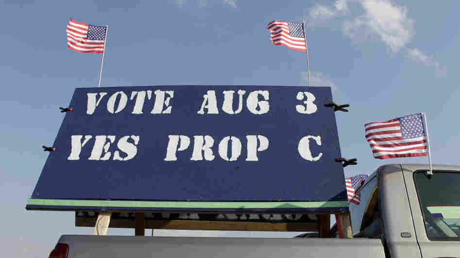 A pickup truck carries a large sign in support of Proposition C outside a rally in St. Charles, Mo.
