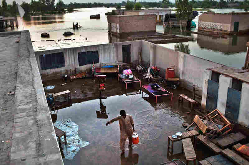 A boy carries water through a flooded yard in the village of Vasandawali in Punjab. The United Nations has appealed for $460 million to deal with the immediate aftermath of the floods, but has warned that billions will be required in the long term, with villages, businesses, crops and infrastructure wiped out.