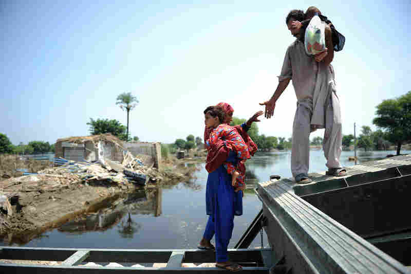 A man helps his wife cross a river in Kasbag Gujarat. The United Nations estimates that 4.6 million people in Pakistan are still without shelter.