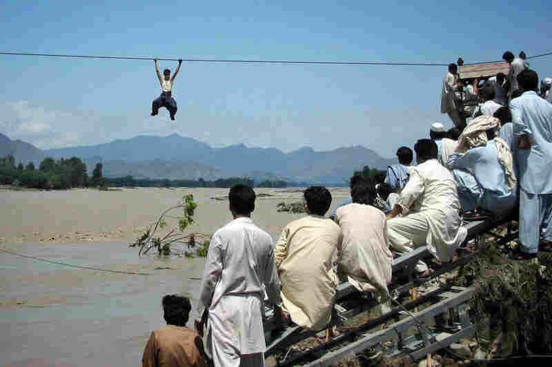 Onlookers perched on a damaged bridge watch a man cross a river by rope Aug. 3 in Swat Valley's Chakdara.