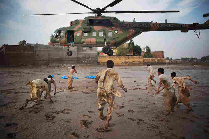 Residents grab water bottles dropped from a Pakistani air force helicopter Aug. 2 in Nowshera, where thousands were affected by the floods.