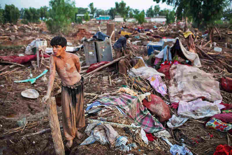A boy takes a moment to rest after salvaging belongings from his destroyed home in Pabbi.