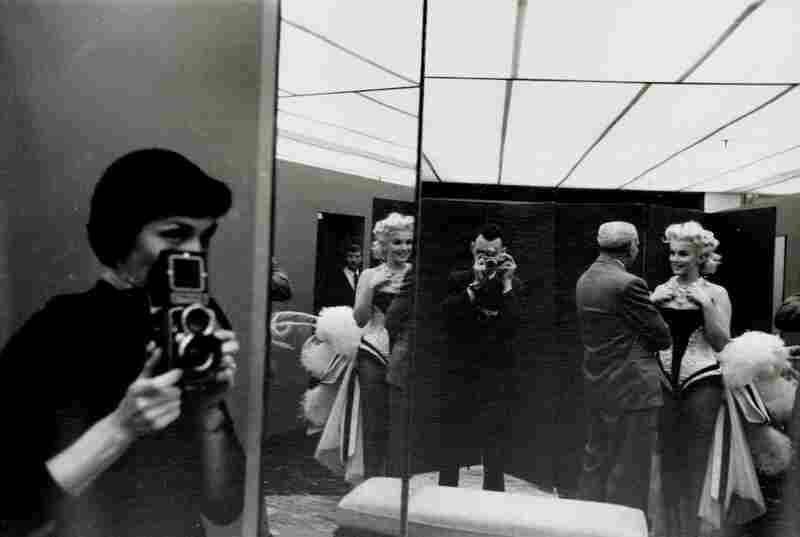 Feingersh makes an appearance in one of his photographs — a reflection of Monroe in a fitting room, 1955.
