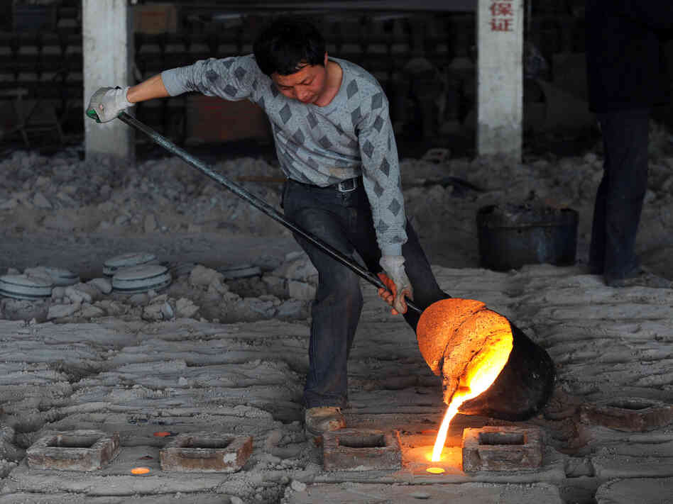 A Chinese worker pours molten steel into