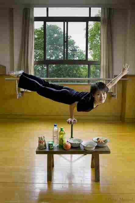 Cao Xiaoli, a professional acrobat, balances on one hand with her daily diet displayed at Shanghai Circus World in China. She is 16 years old, 5 foot 2 and 99 pounds, and on a typical day in June, her caloric intake was 1,700. A few food items in the photo: yogurt, zha paigu (pork ribs), noodles, egg, broth, green tea.