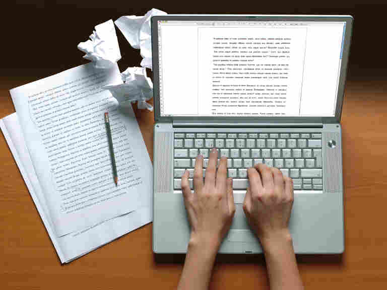 Hands typing on a keyboard with papers