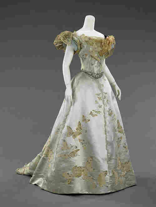 An extravagant French ball gown made of blue silk satin, sequins, rhinestones, beads and metallic [word missing]. In the late 19th century, American women were still taking their style cues from Europe.