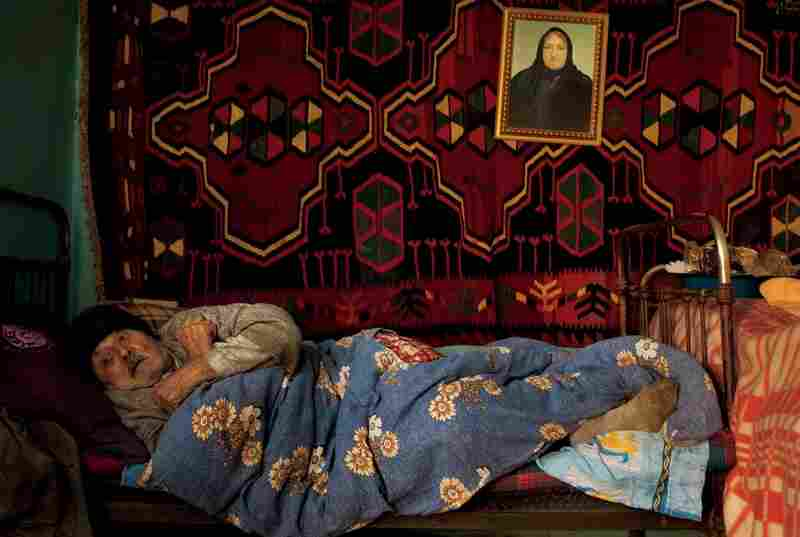 An Azerbaijani refugee huddles in his Baku home beneath a picture of his late wife. When ethnic Armenians won control of the enclave of Nagorno-Karabakh in the early 1990s, nearly 800,000 Azerbaijanis fled. Allied with Turkey, Azerbaijan has also made efforts to exclude the Christian Armenia.