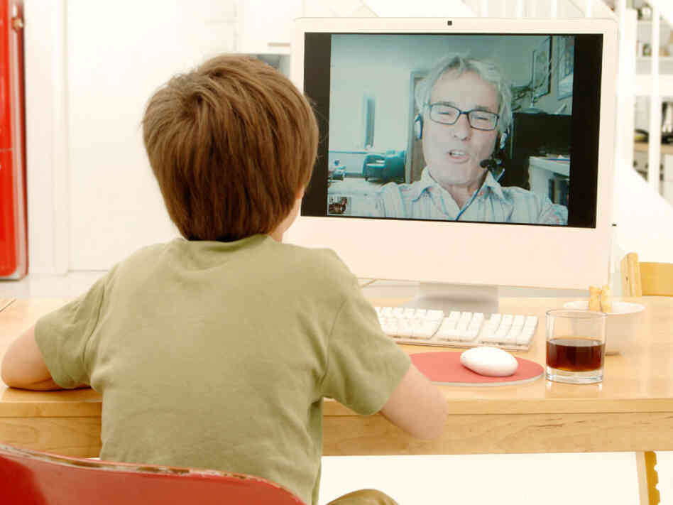 A child videochats with his grandfather.