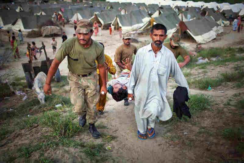 Suffering from high fever and spasms, Allah Detta is carried by soldiers as he is rushed to receive medical treatment in the Sultan Colony army flood relief camp. Military and aid organizations are struggling to cope with the scale of the disaster, in which more than 1,600 people have died and millions have been displaced.