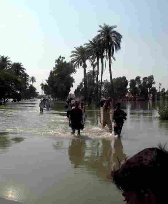 Survivors wade through flood waters washing over the main road connecting the southern Punjab cities of Dera Ghazi Khan and Muzaffargarh. Residents in the village of Bahawal Nala say that some 25 to 30 people have drowned trying to cross the main road that is now five feet under water.
