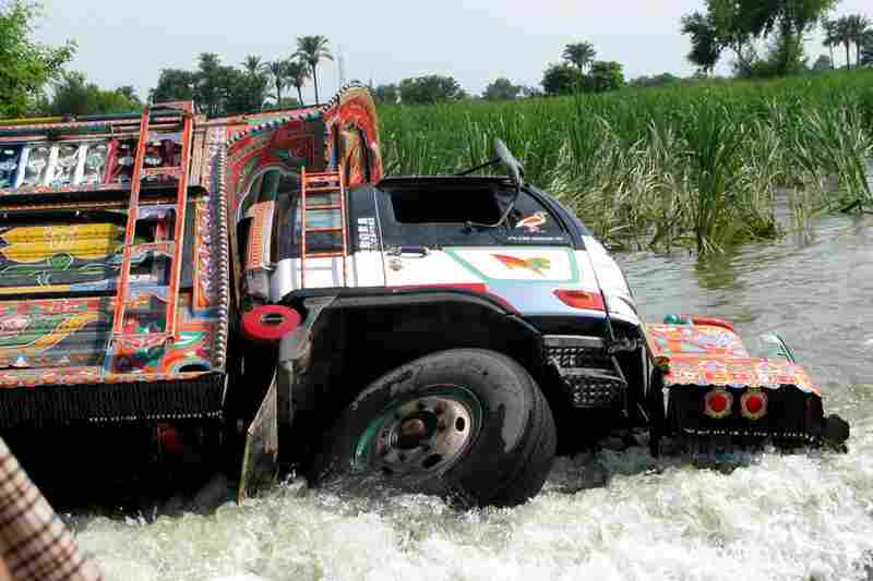An overturned truck is seen on the main Dera Ghazi Khan-Muzaffargarh Road. The flood waters from the Indus River have buried long stretches of the road. Although many villages are accessible by boat — they are in short supply, leading many to attempt the dangerous crossings in trucks, with deadly consequences.