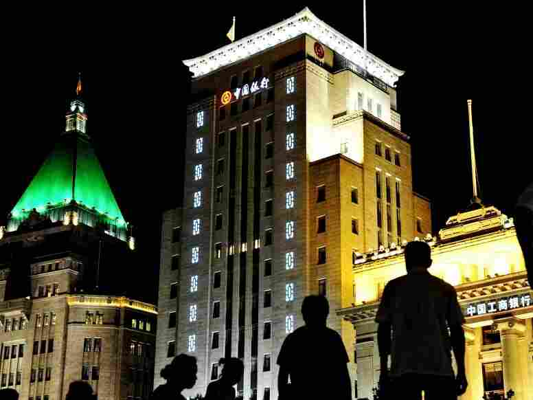 People are silhouetted on the Bund - the