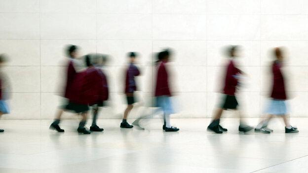 Kids walk down a hall.