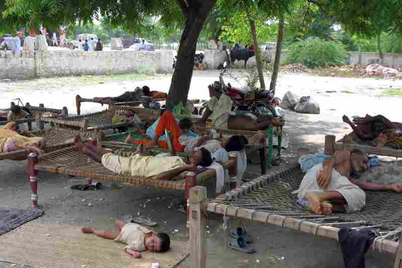 """Families rest from the heat in the village of Baseera. Curled up on  traditional """"charpoys"""", people have been forced to take shelter under the sky as large parts of their village were submerged."""