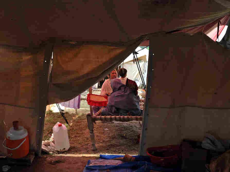 Pakistani flood survivors sit in a tent