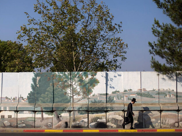 An Israeli man walks next to a concrete wall in the Jewish neighborhood of Gilo in Jerusalem. Israel is removing the concrete barrier put in place after Palestinian gunman targeted the suburb in 2000 from the nearby Palestinian village of Beit Jala. The military said the wall is coming down because of a reduced security threat and increased coordination with Palestinian security forces.