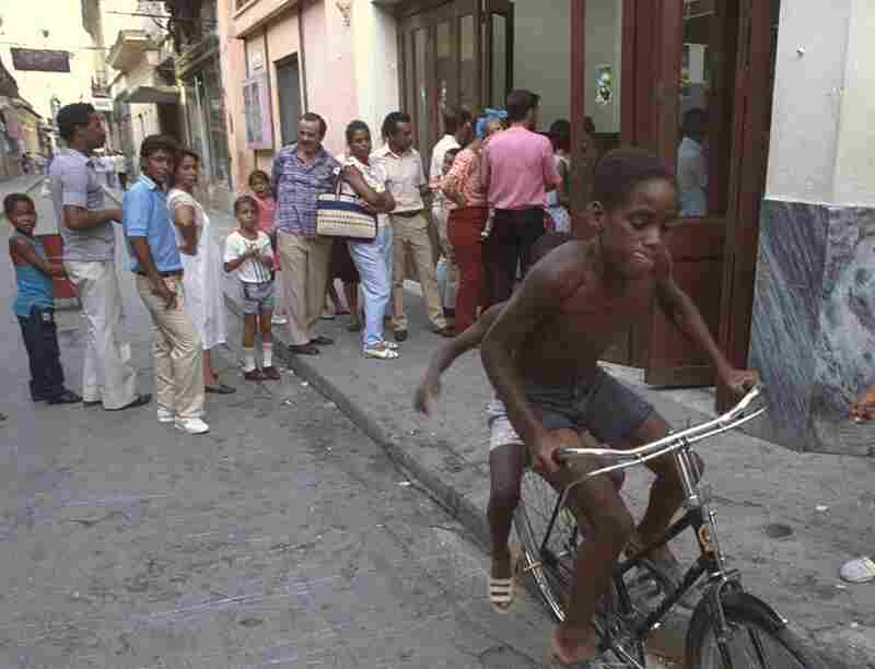 Two children play on a bike while dozens of Havana residents wait in line for milk and rice on July 29, 1991.  Cuba lost financial aid after the Soviet Union collapsed.