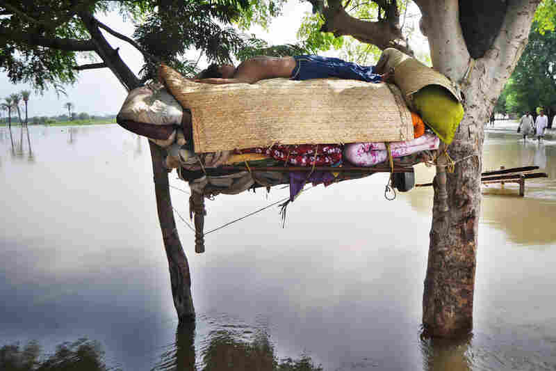 A flood survivor sleeps on a hammock Aug. 13 in Shah Jamal village.