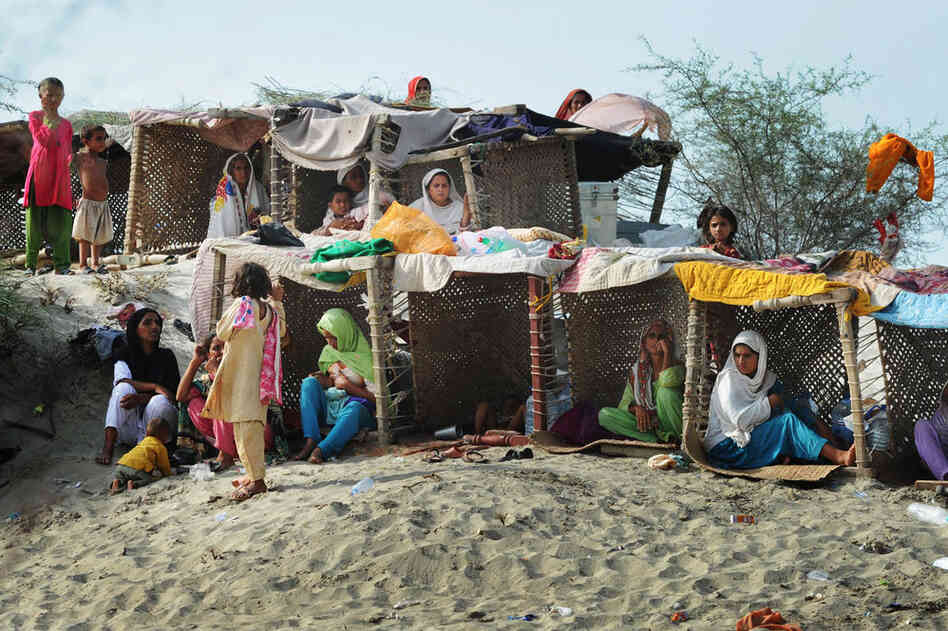 Pakistanis displaced by floods take shelter in temporary tents made with charpoys (bedsteads) near a makeshift camp in Baseera in Punjab province on Aug. 26. The United Nations warned that 800,000 people in desperate need of aid had been cut off by the deluge across the country and appealed for more helicopters to deliver supplies to those people reachable only by air.