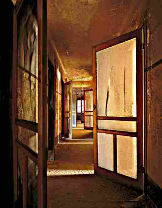 "Nurse's Quarters, Island 3. ""I remember climbing a dark staircase to discover the floor where the nurses slept. Screen doors were open at various angles, creating an almost mystical pattern in the space."""