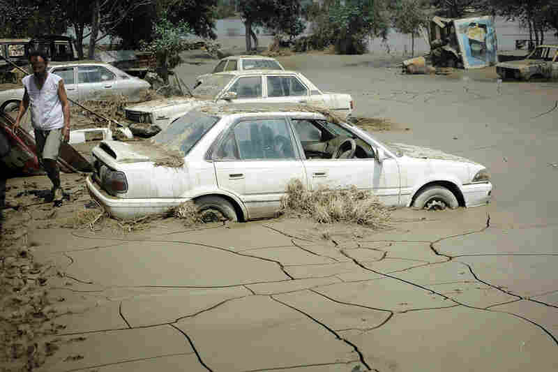 Dried mud surrounds cars Aug. 5 in Nowshera.