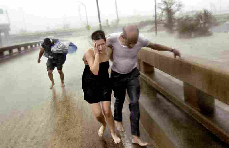 Otis Brown, 67, holds on to Jennifer Cooper, 33, as they fight their way through the wind driven rain of Hurricane Katrina with Albert Jean, 50, up an Interstate 610 off-ramp after escaping roof-level floodwaters in the Clermont Driver area of New Orleans. The three were part of a larger group who escaped the floodwaters by taking an aluminum motorboat to the off-ramp on Aug. 29, 2005. (Jim Win...